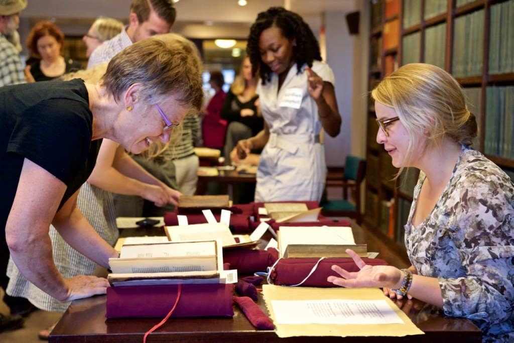 Student Curators invite public audiences to leaf through 16th C books as part of a Holding History event (Photo: Rick Marolt)